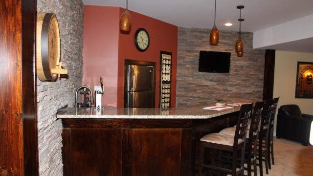 Basement remodel with custom bar and stone accent wall